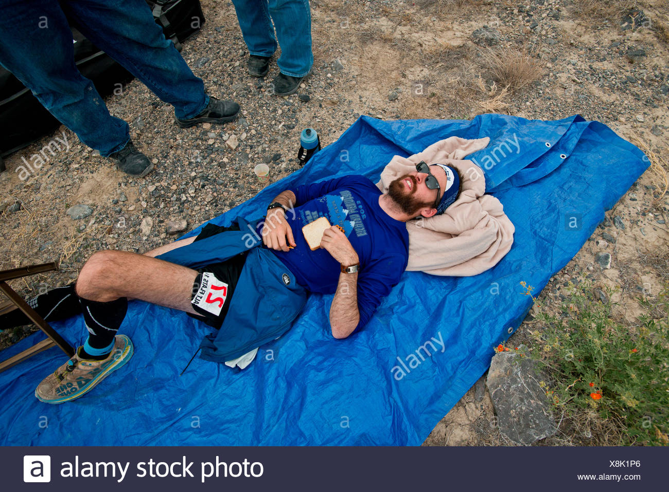 A competitor lays exhausted on a tarp during the Salt Flats 100 in Bonneville, Utah. - Stock Image