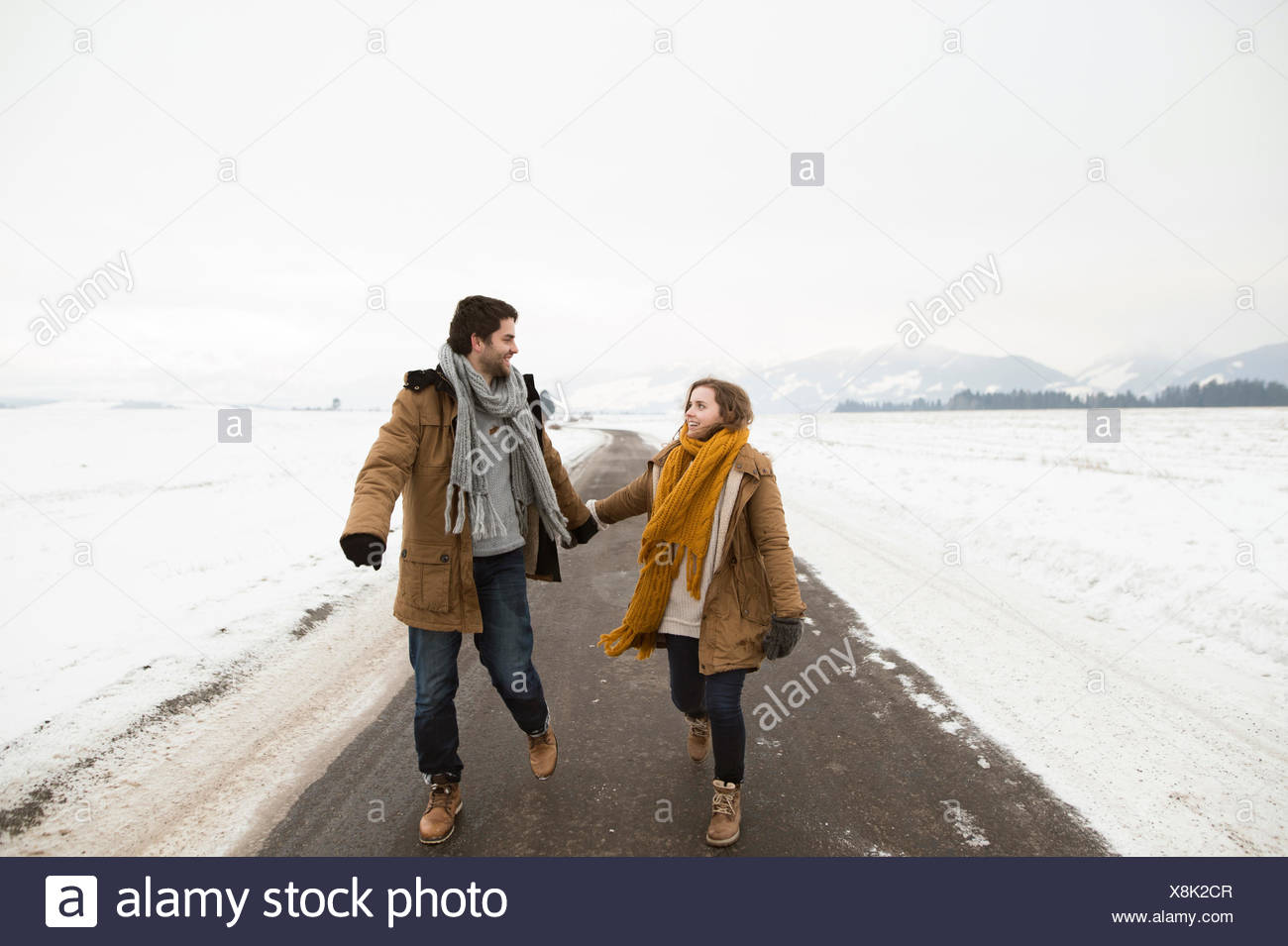 Young couple in love walking on empty country road in snow-covered landscape - Stock Image