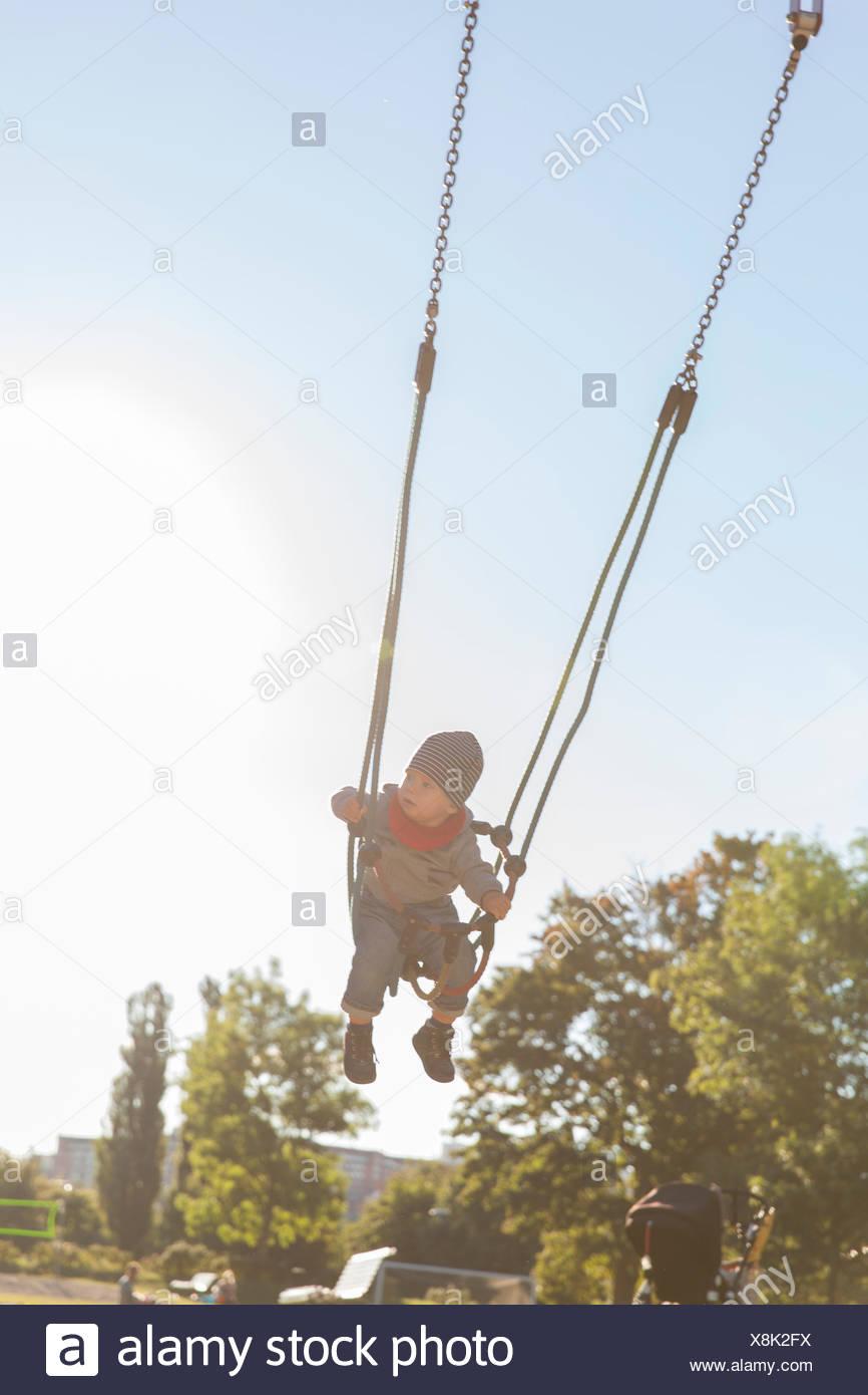 Sweden, Stockholm, Boy (12-17 months) swinging outdoors - Stock Image