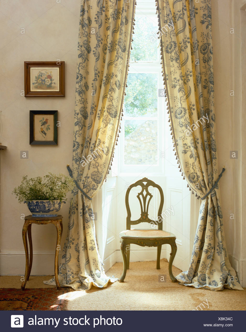 Antique chair in front of tall window with pastel blue patterned curtains edged with bobble trimming