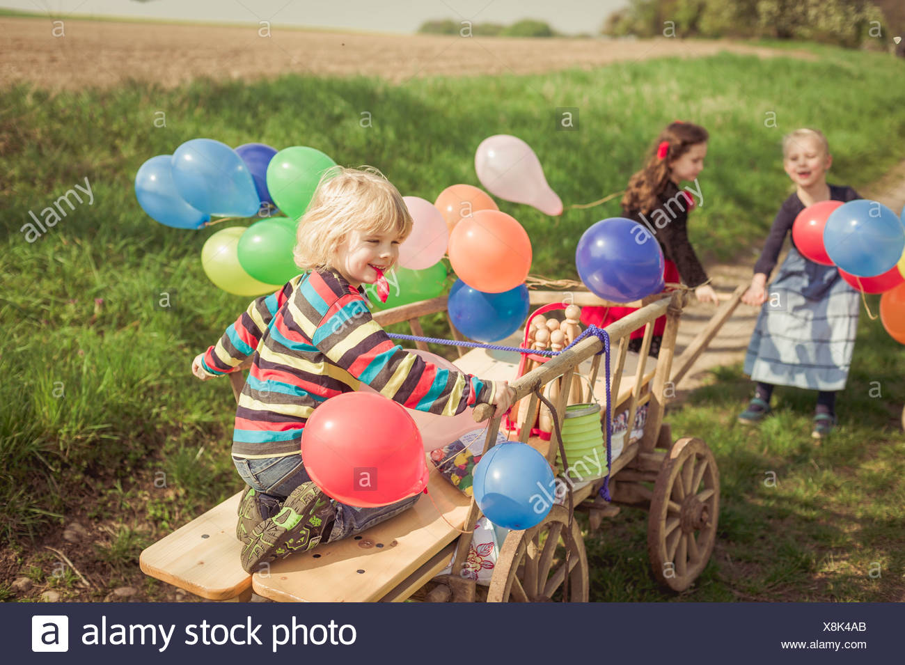 Three children on the move with wooden trolley and balloons - Stock Image