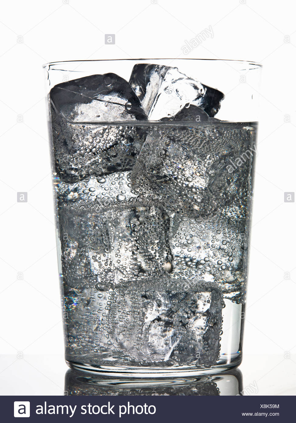 Glass of ice cubes in fizzy drink - Stock Image