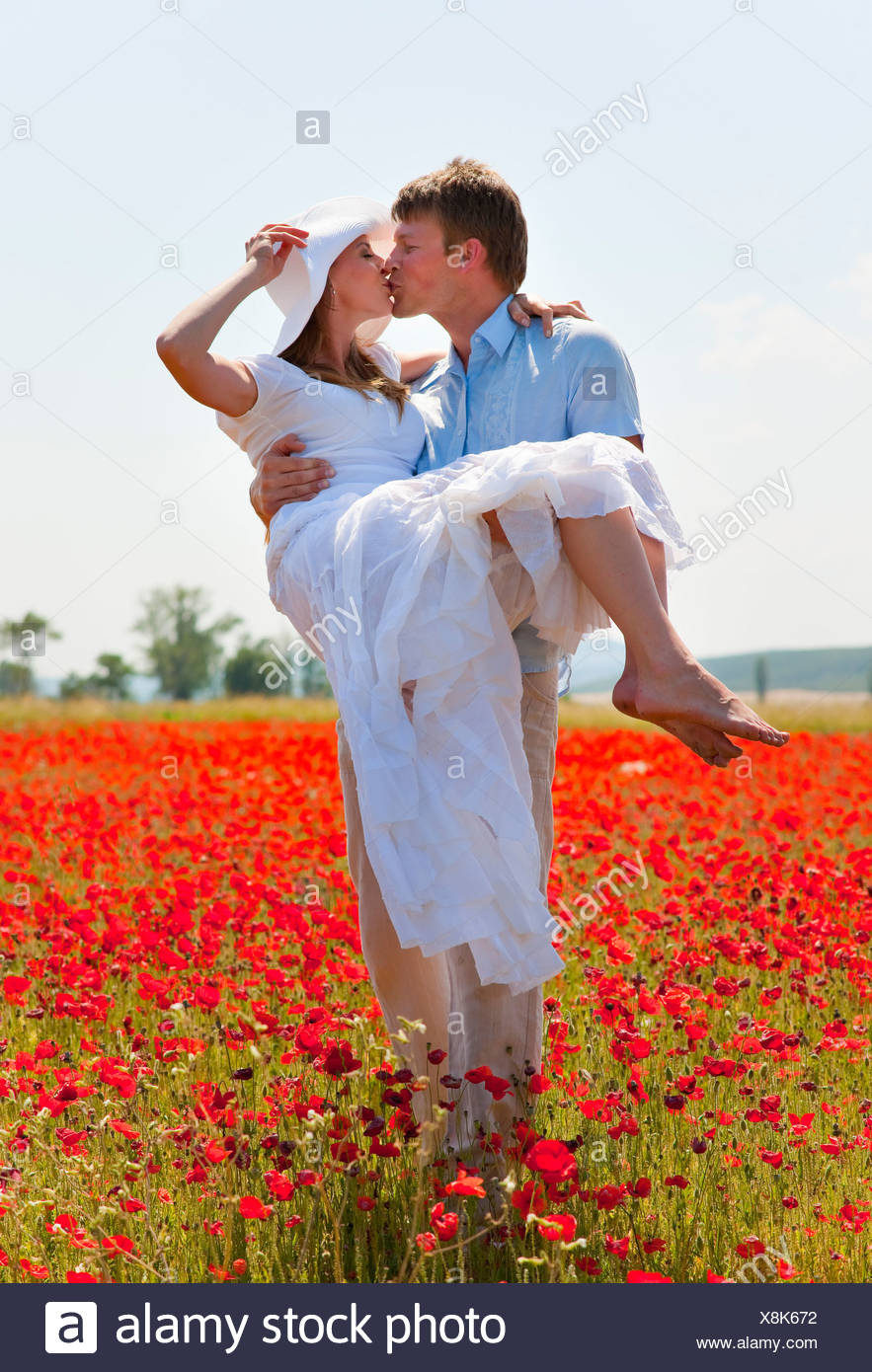 Couple kissing in field of poppies - Stock Image