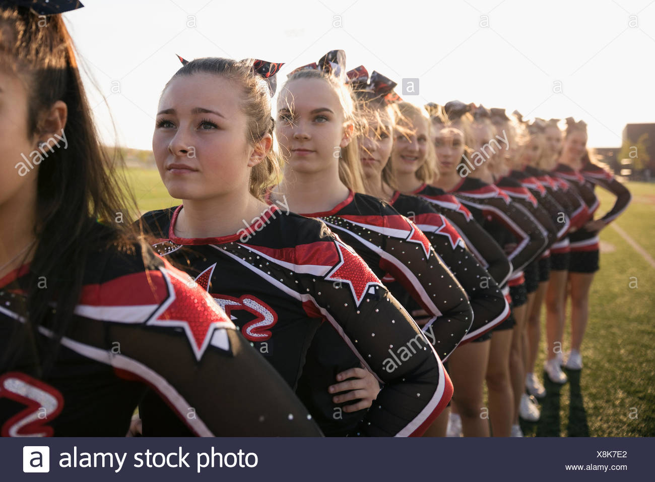 Teenage girl high school cheerleading team poised, standing in a row - Stock Image