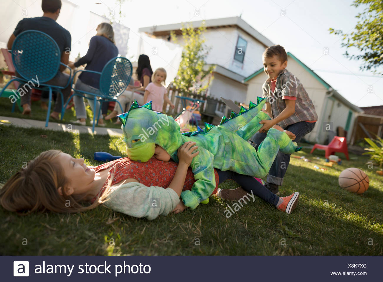 Brother in dinosaur costume tackling, playing with sister in backyard - Stock Image