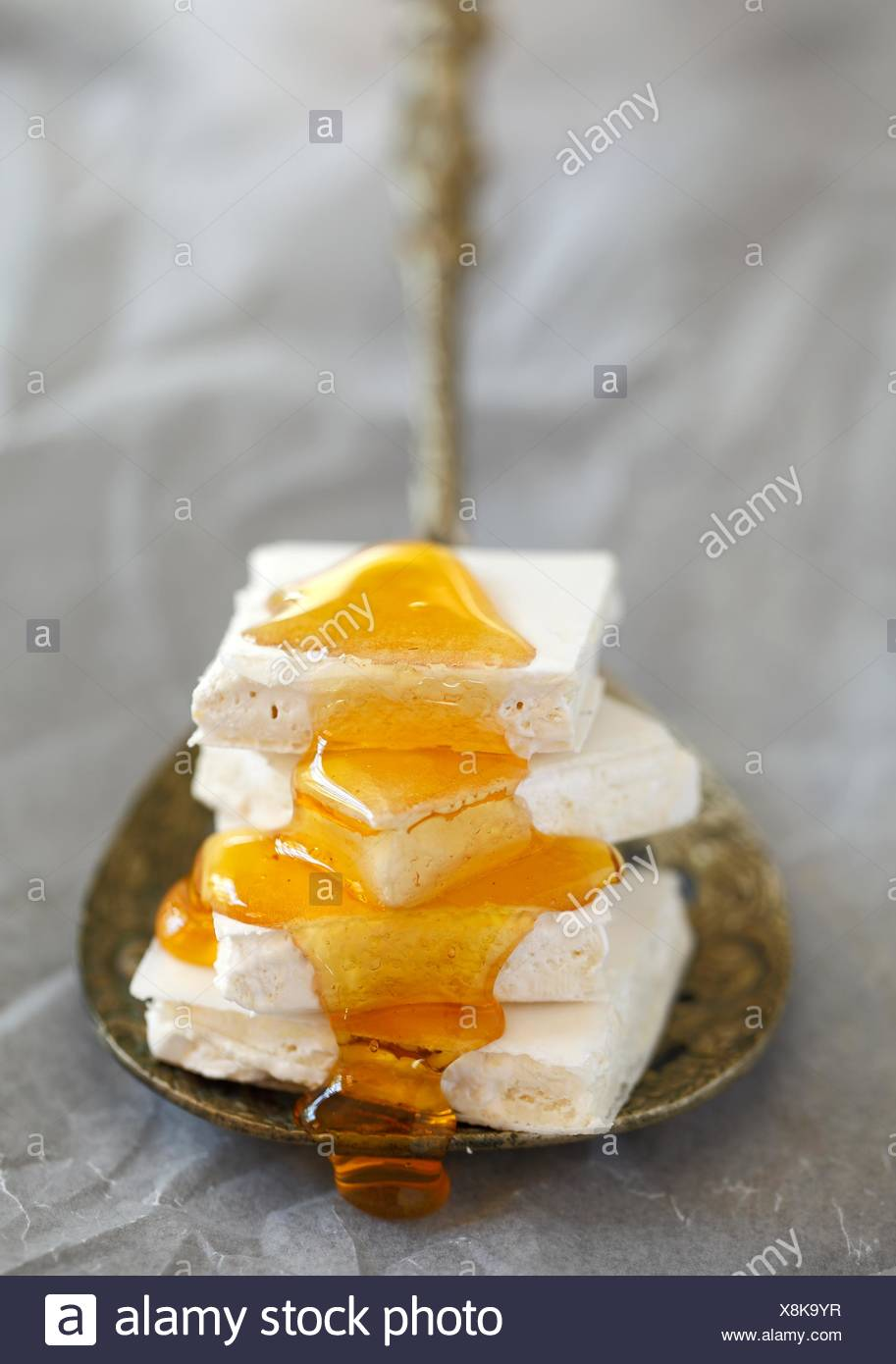 Square pieces of white, plain nougat in stack on metal spoon covered in drizzled honey - Stock Image