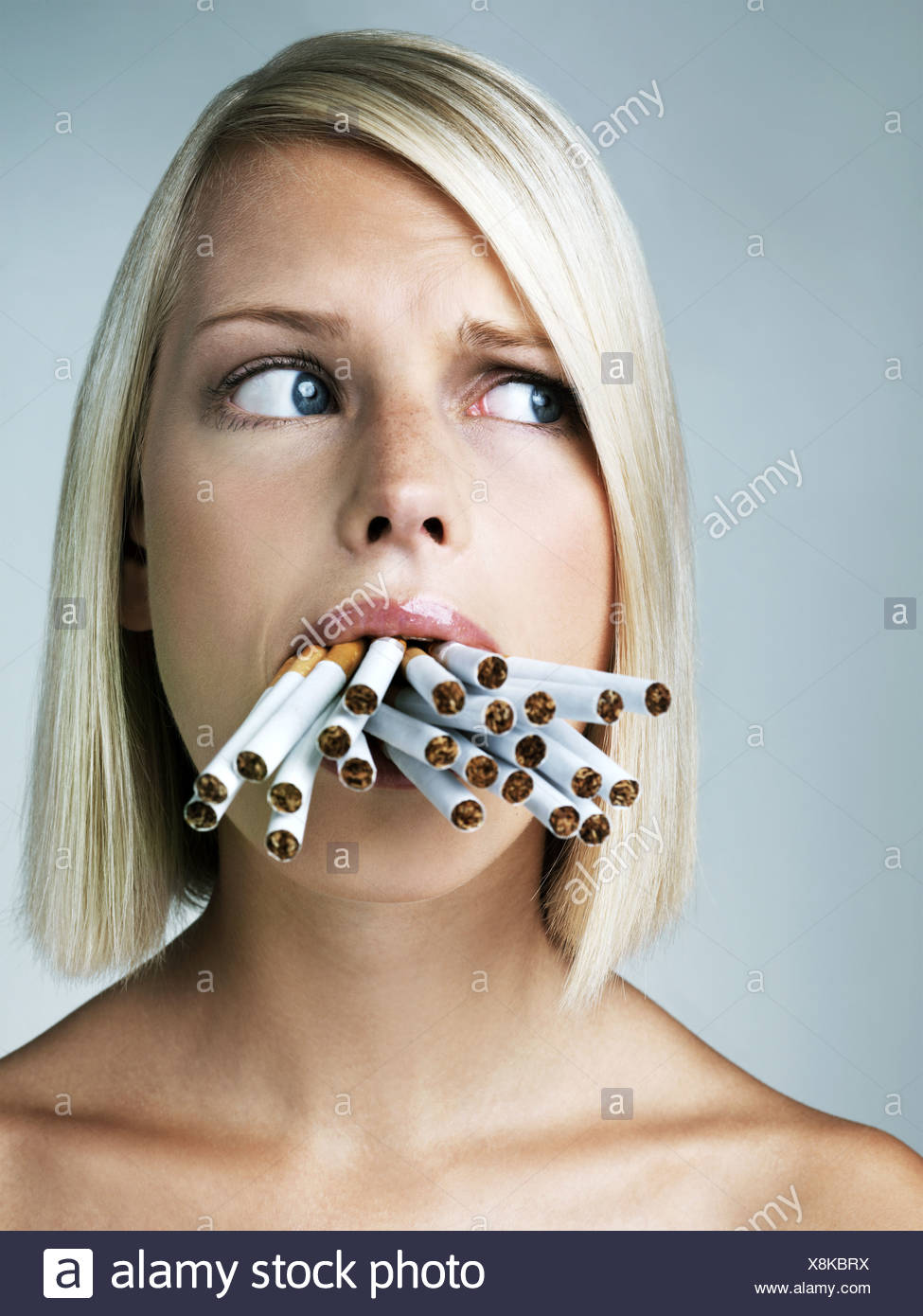 Studio Portrait Of Young Woman With Mouthful Of Cigarettes Stock