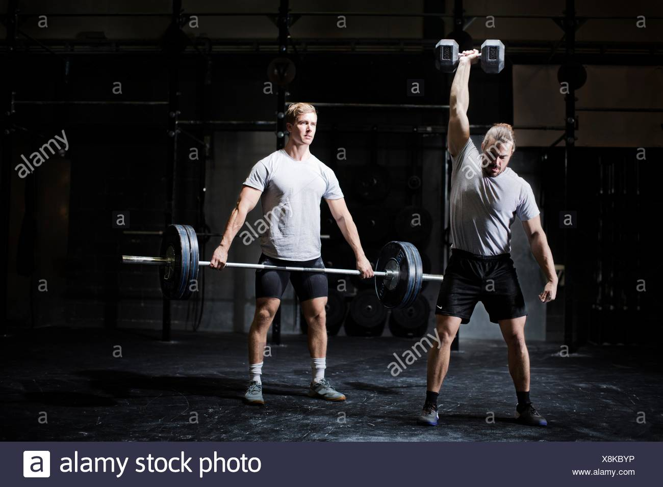 Two young men weightlifting with dumbbell and barbell in dark gym - Stock Image