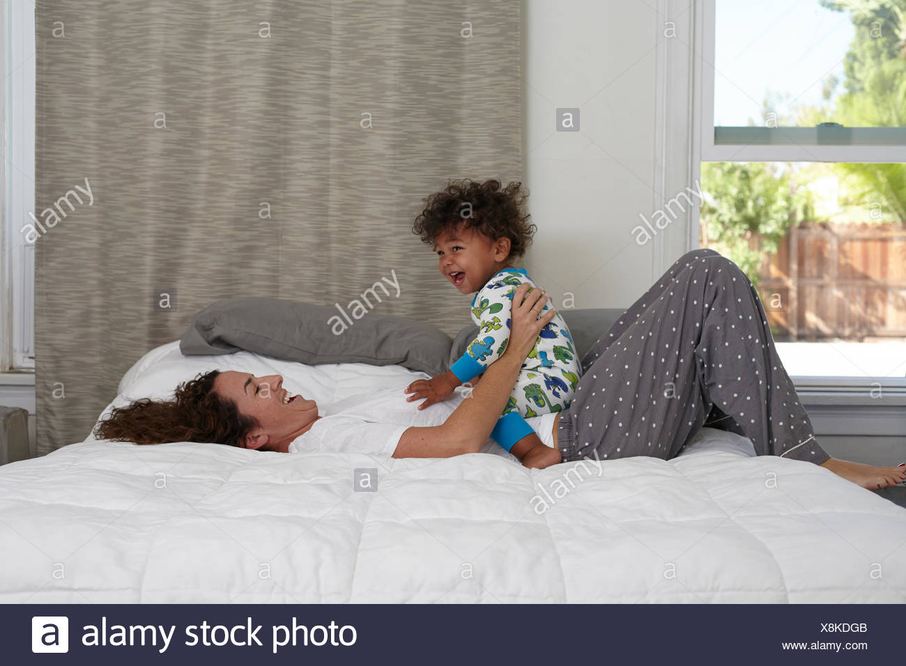 Male toddler sitting on top of mother on bed - Stock Image