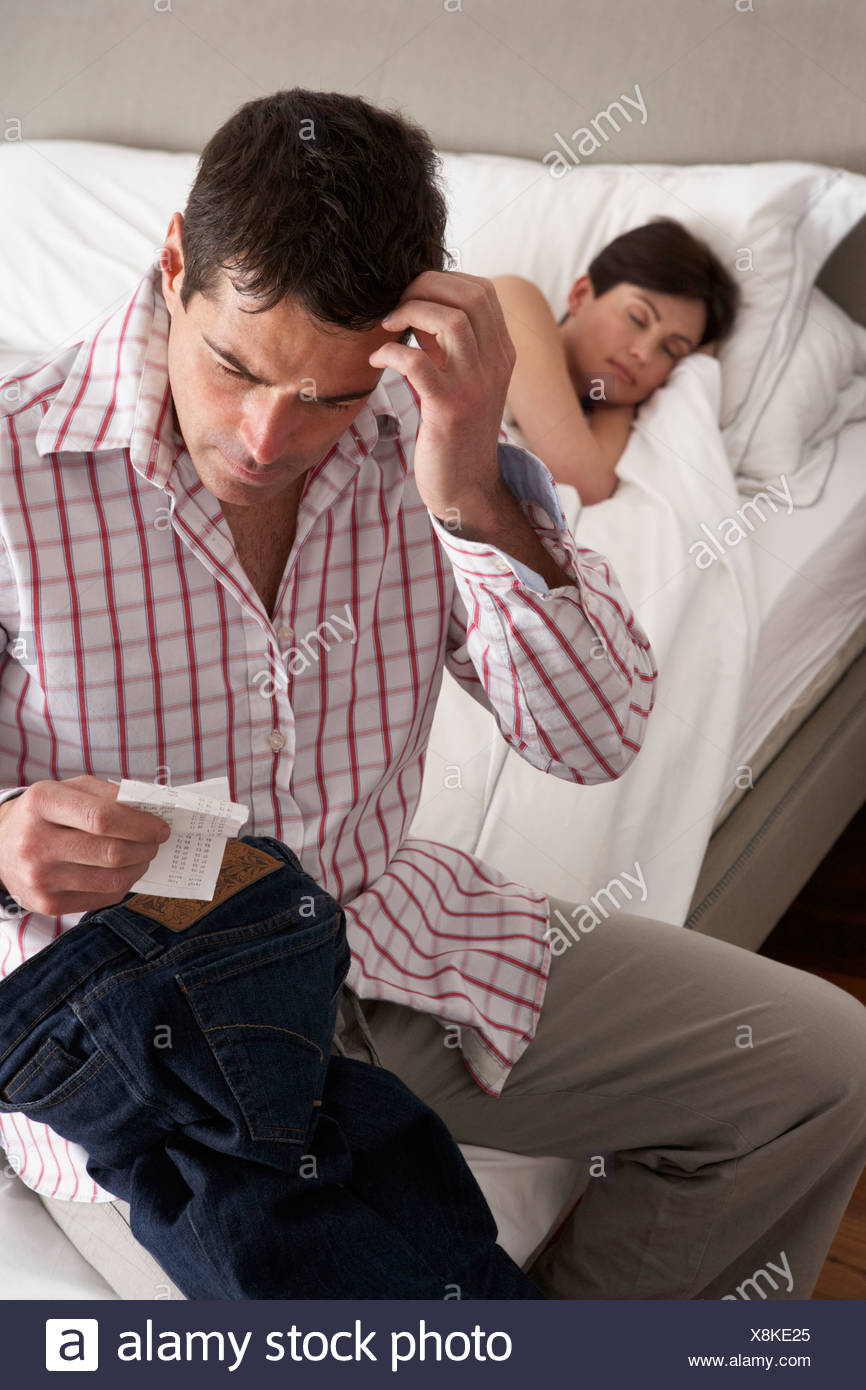 Suspicious Husband Finding Receipt In Wife's Pocket Whilst She Sleeps - Stock Image