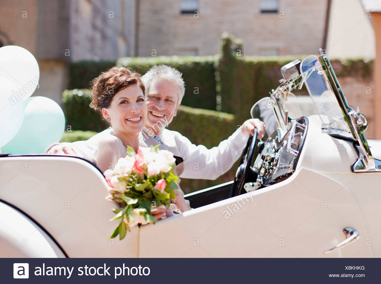 mature bride and groom riding in convertible stock photo: 280714100