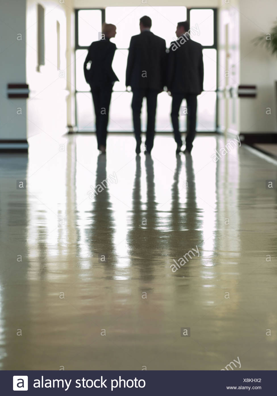 Business people walking in lobby - Stock Image