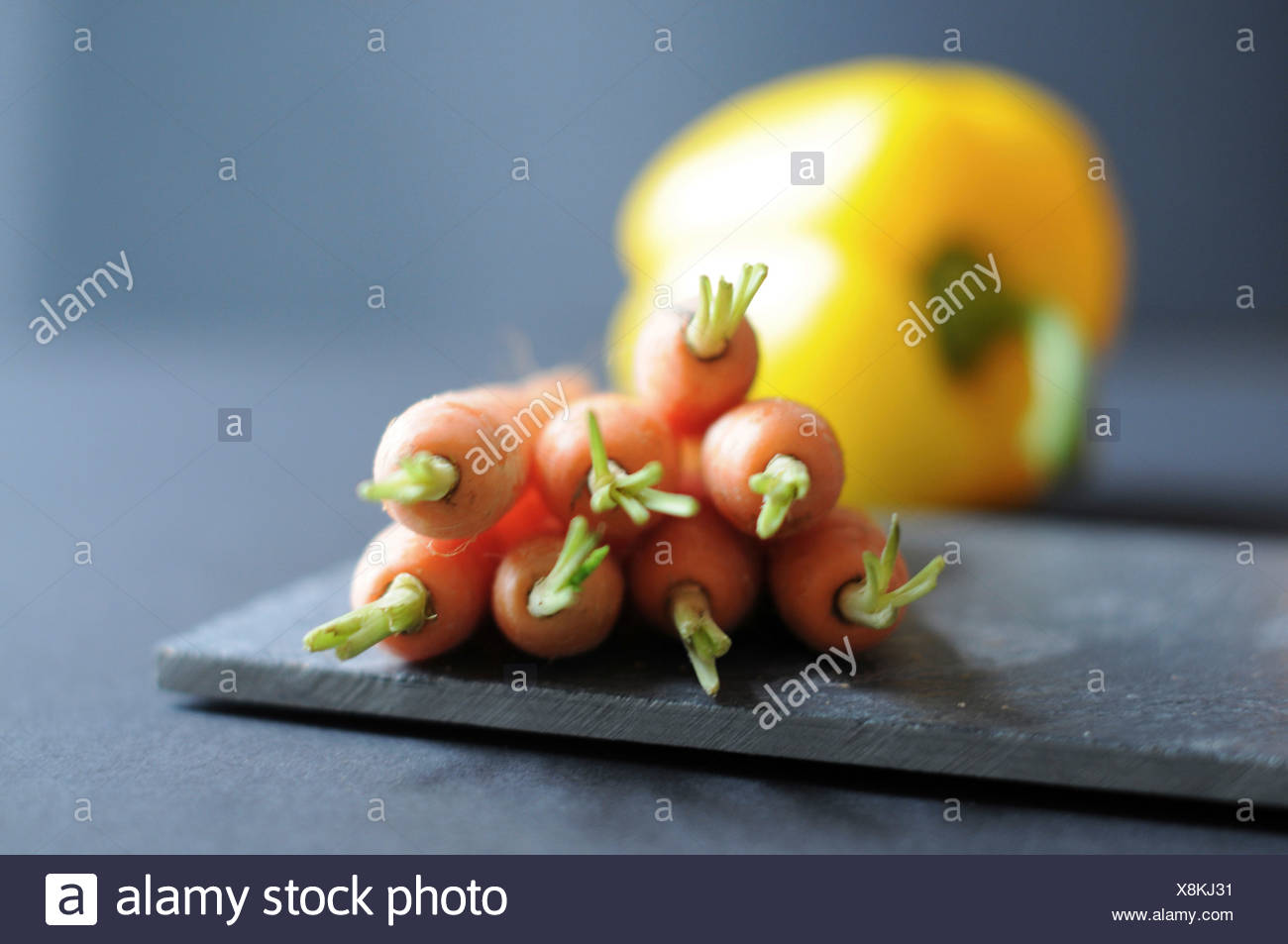 Carrots and one yellow sweet pepper bell - Stock Image