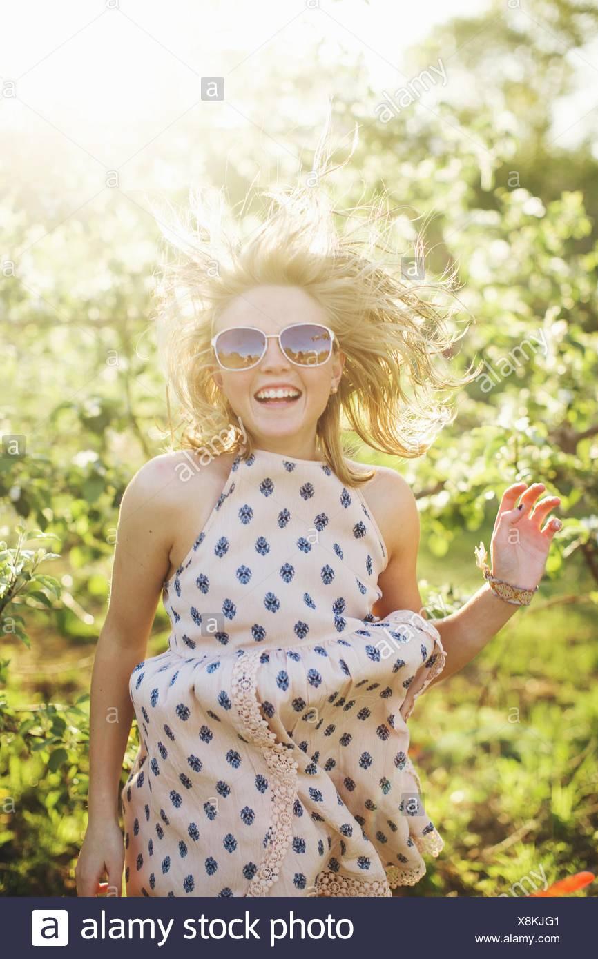 Young woman wearing sleeveless dress and sunglasses jumping looking at camera smiling - Stock Image