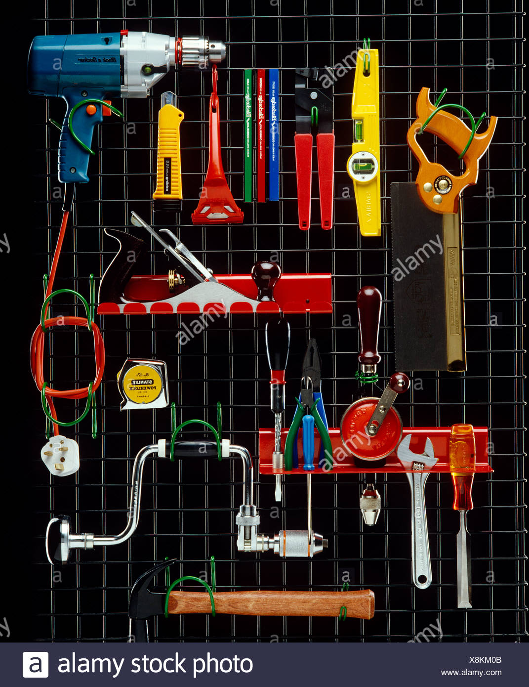 Various tools on metal grill with black background - Stock Image