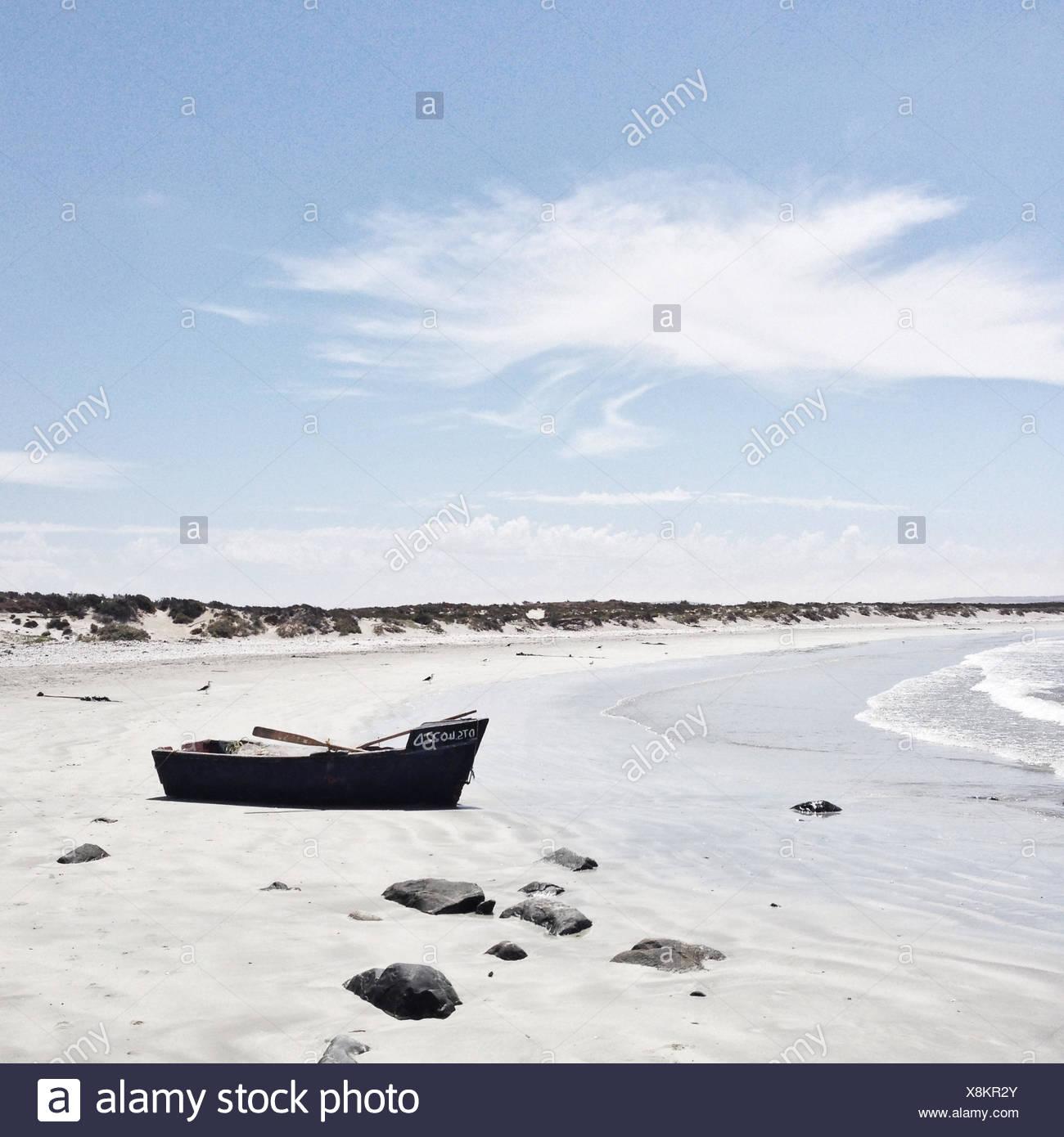 Abandoned boat on beach - Stock Image