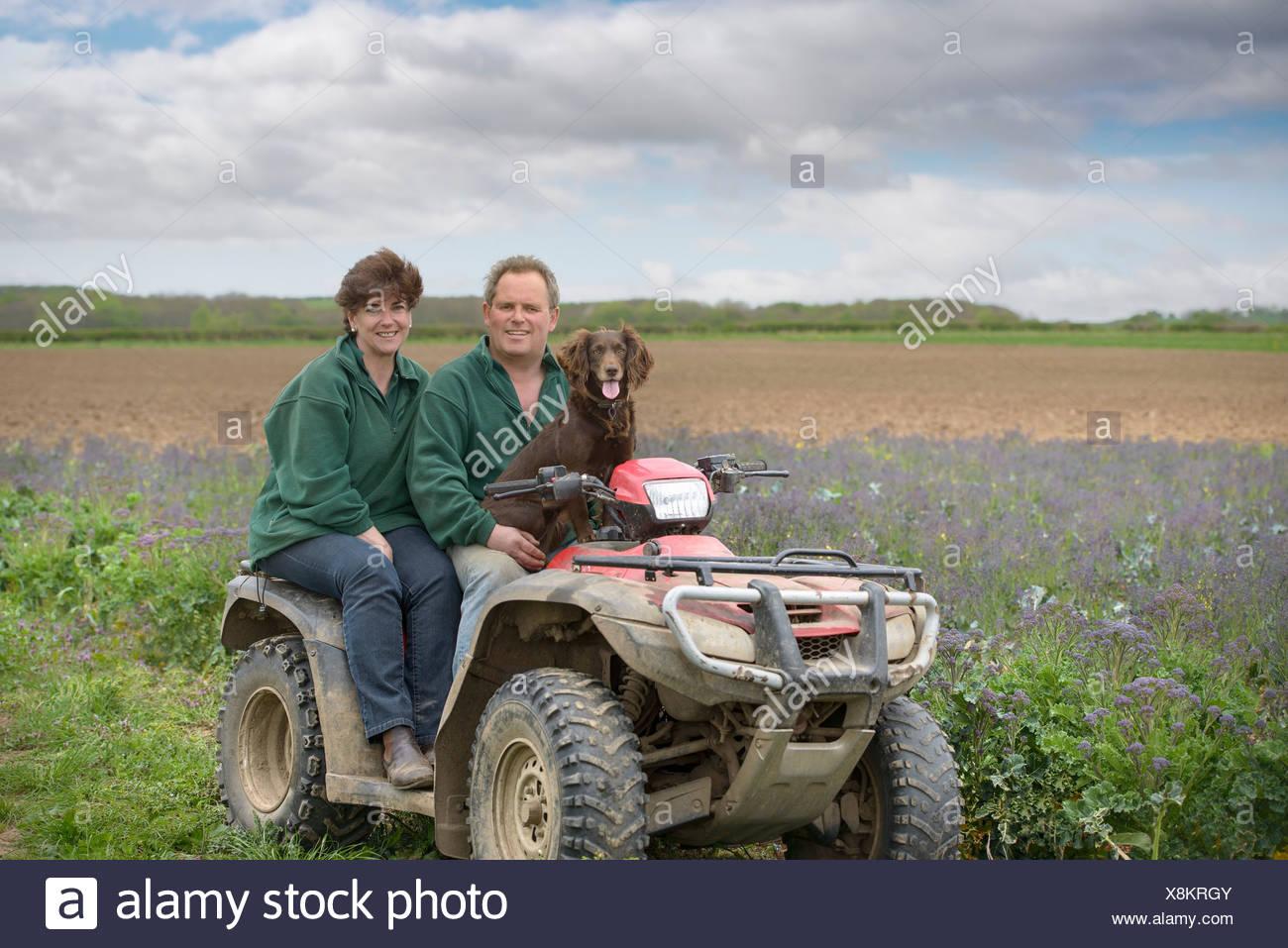Farmer, wife and pet dog on quad bike in field of organic farm - Stock Image