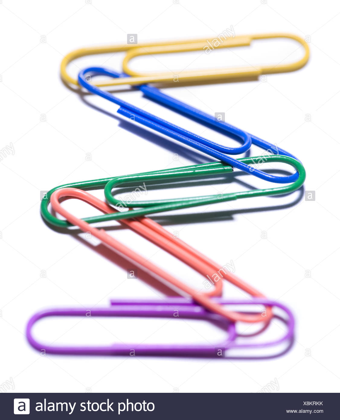 Multi coloured paperclips attached - Stock Image