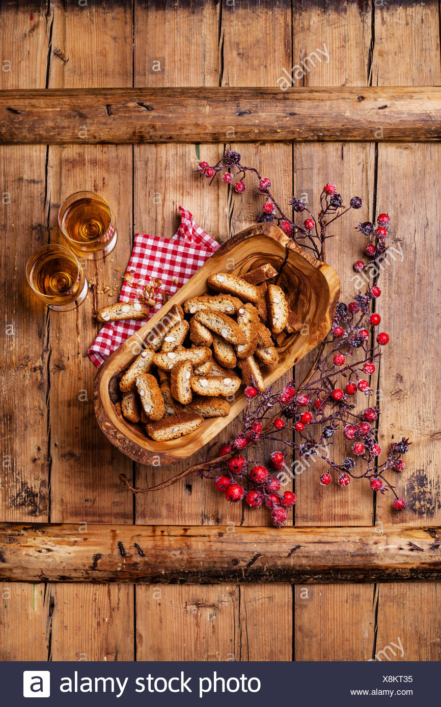 Cantucci in olive wood bowl on wooden background - Stock Image
