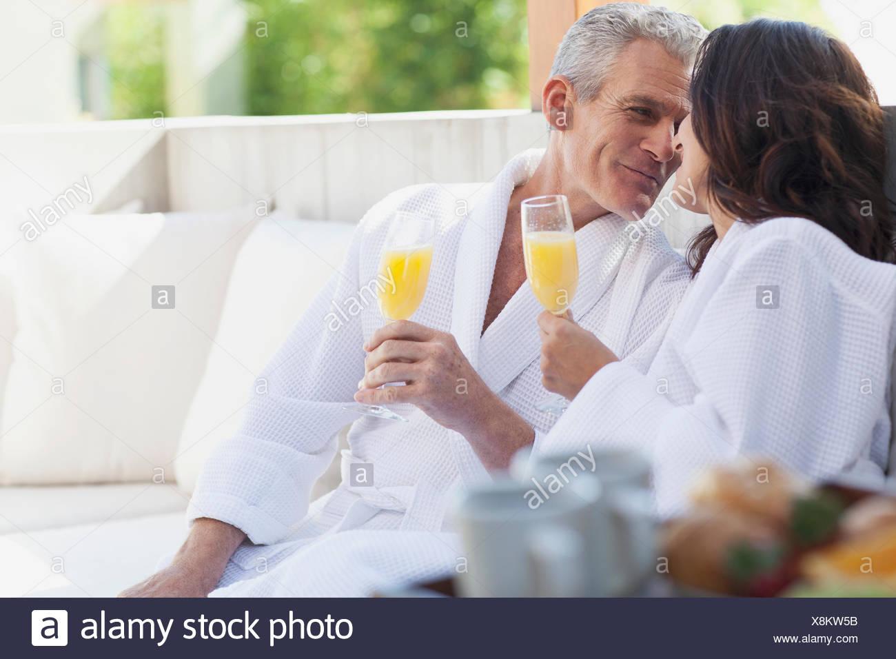 couple in robes drinking orange juice - Stock Image