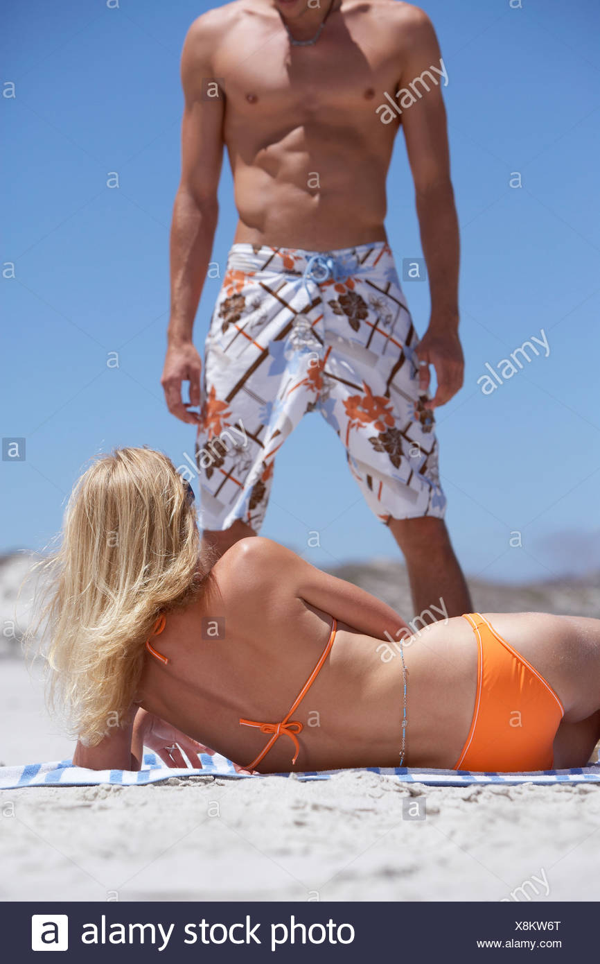 Young woman in orange bikini lying on beach looking up man in swimming shorts surface level - Stock Image