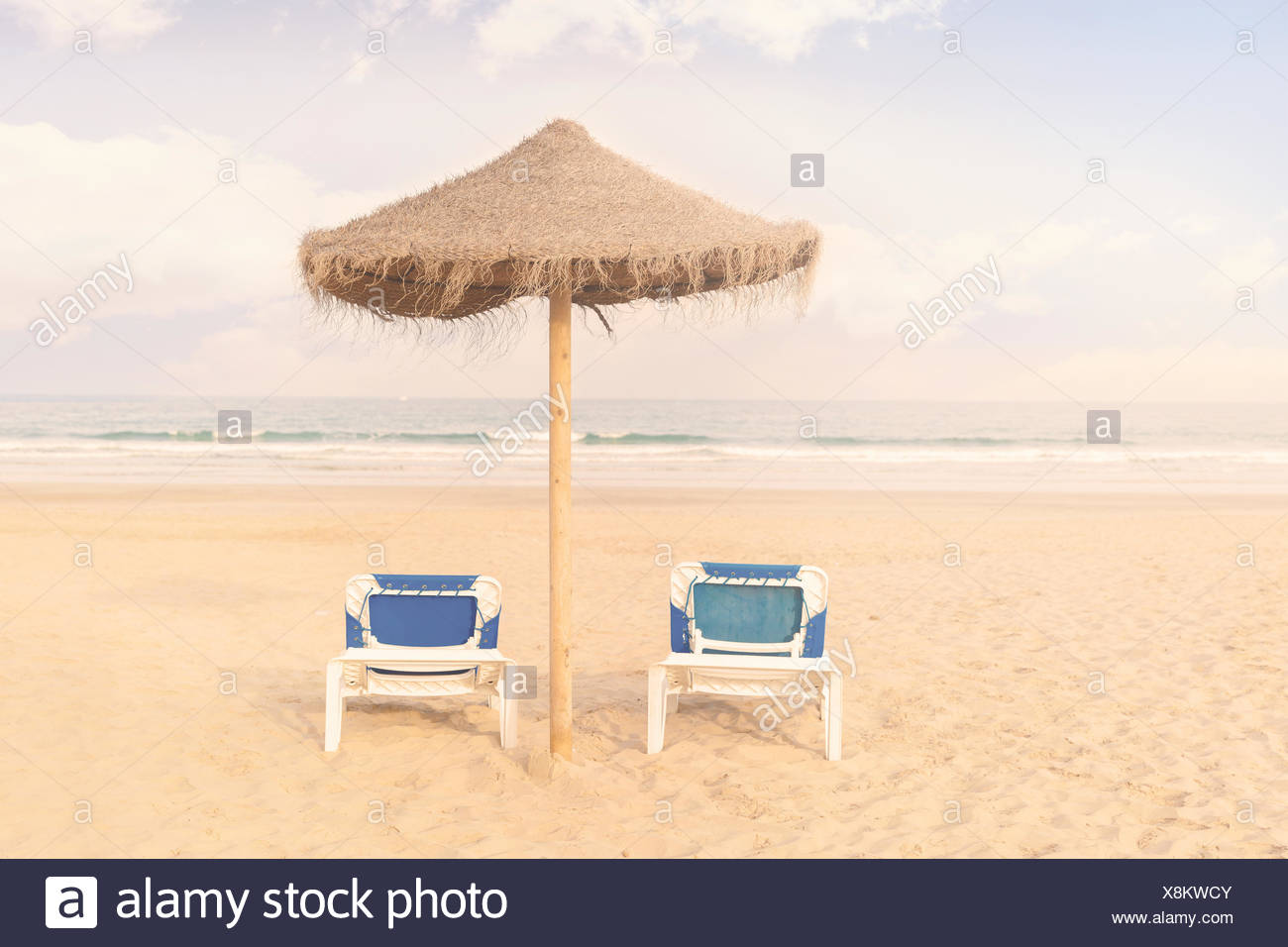 Two sun loungers and a parasol on beach - Stock Image