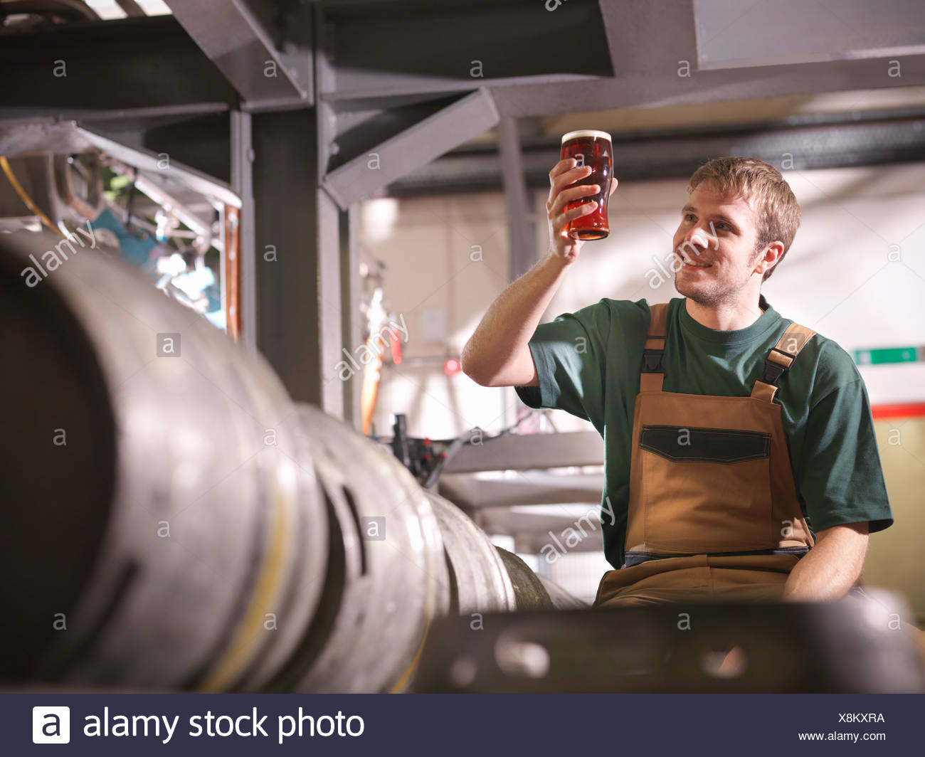 Worker holding pint of beer in brewery - Stock Image