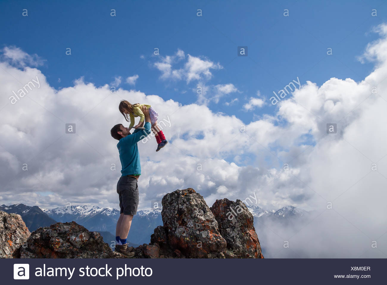 Man holding his daughter in the air - Stock Image