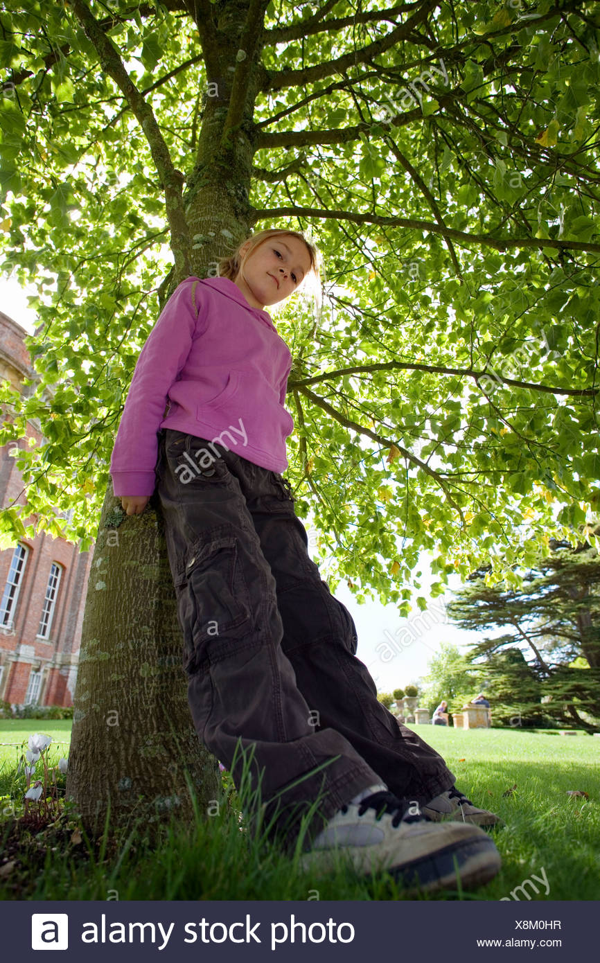 Girl 7 9 wearing purple top and combat trousers leaning against tree trunk in garden head cocked portrait low angle view - Stock Image
