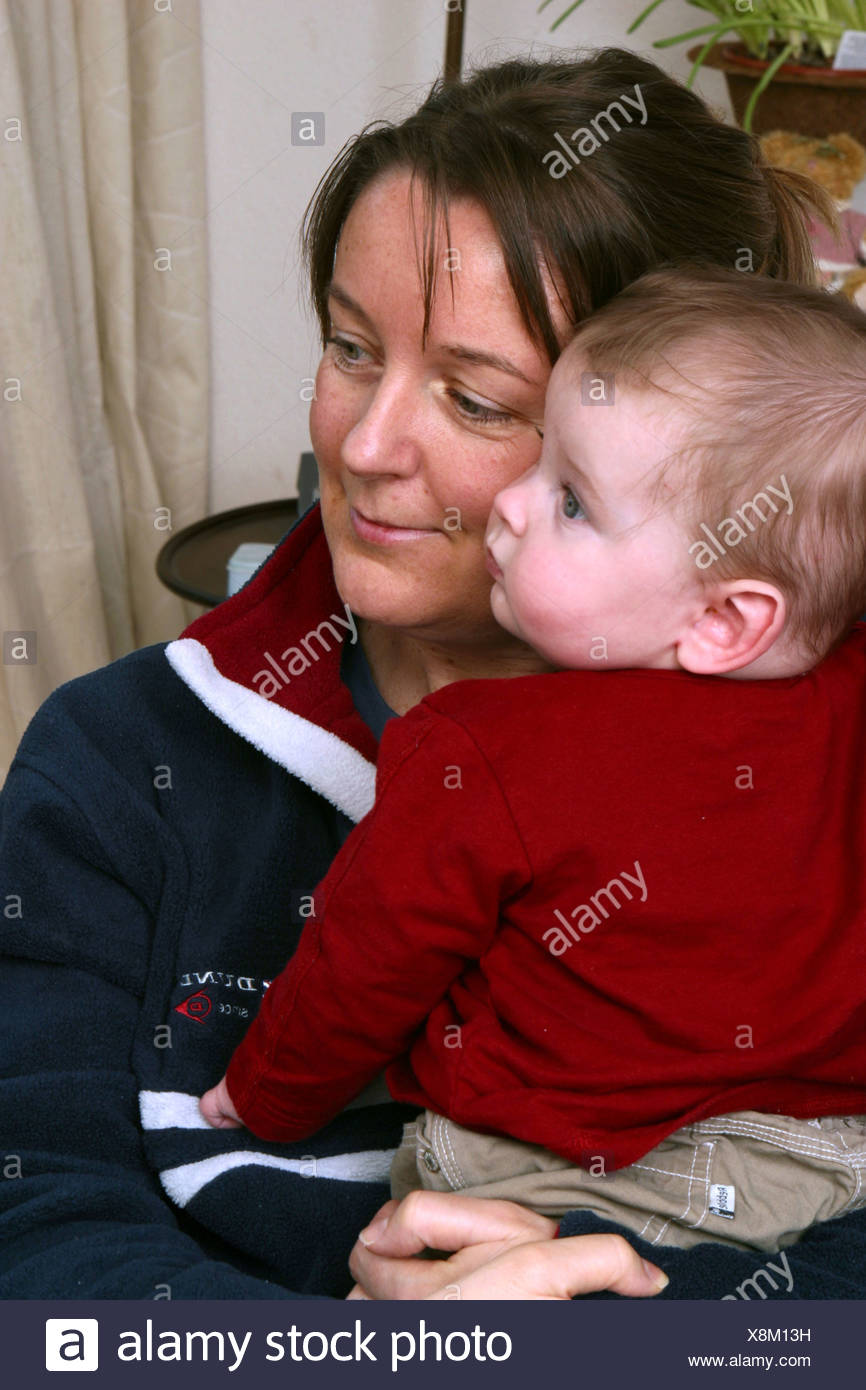 Satisfied mum hugging baby boy - Stock Image