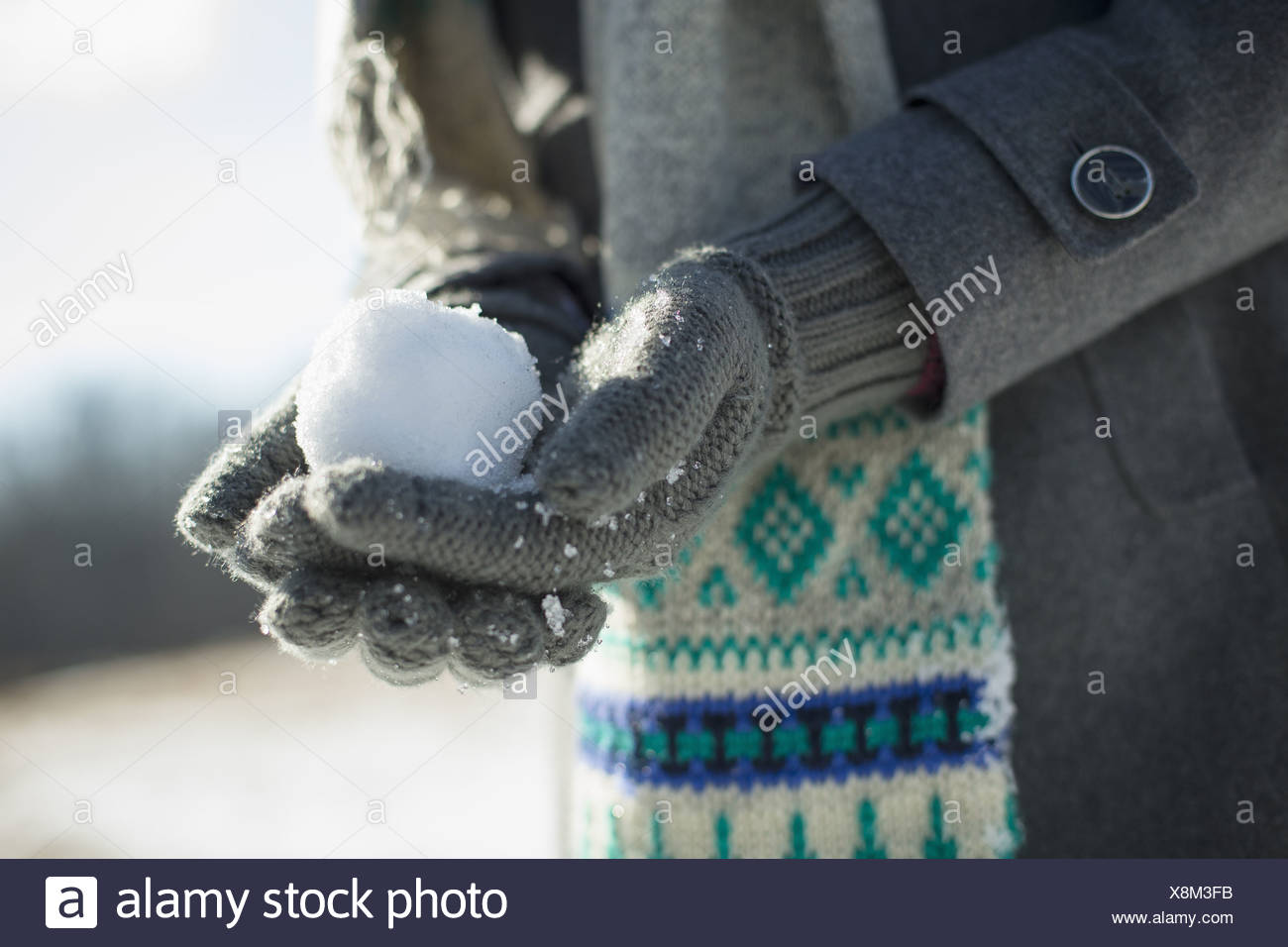 A young woman holding a small snowball in her gloved hands. Stock Photo