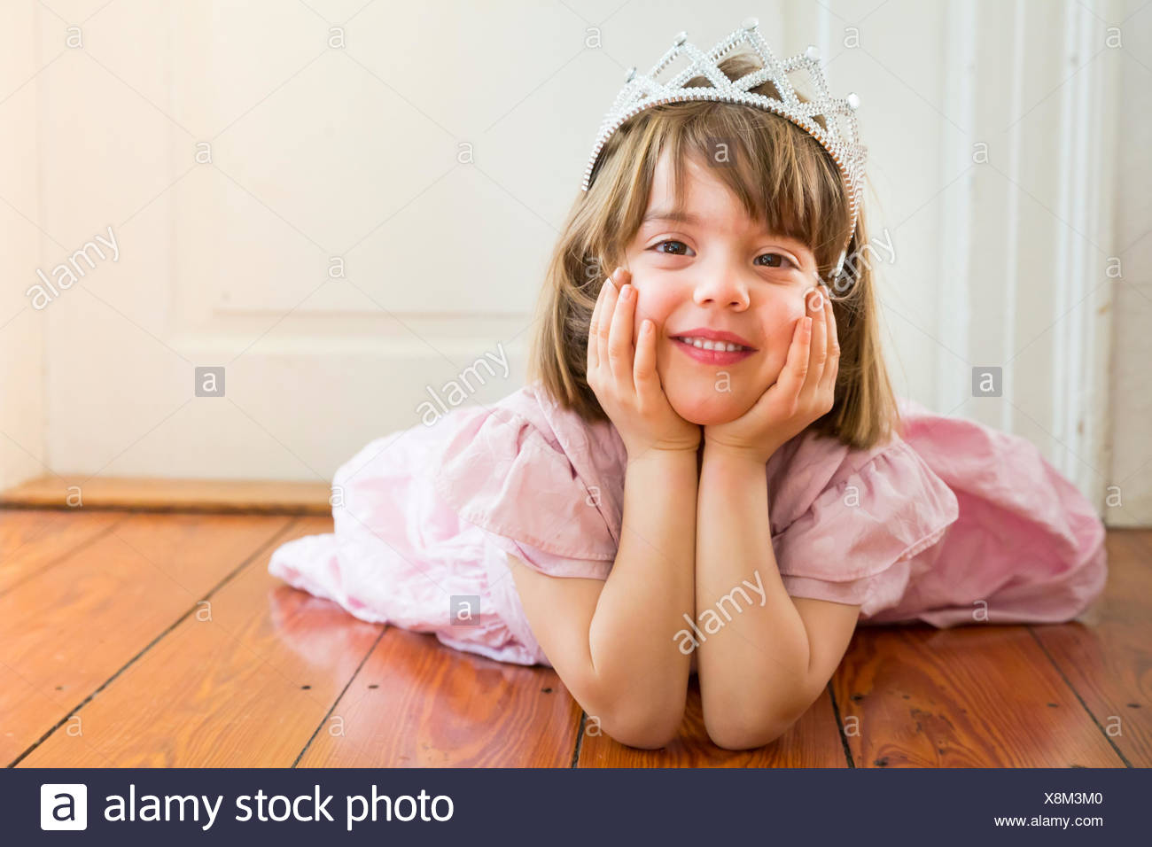 Portrait of smiling little girl dressed up as a princess lying on wooden floor Stock Photo