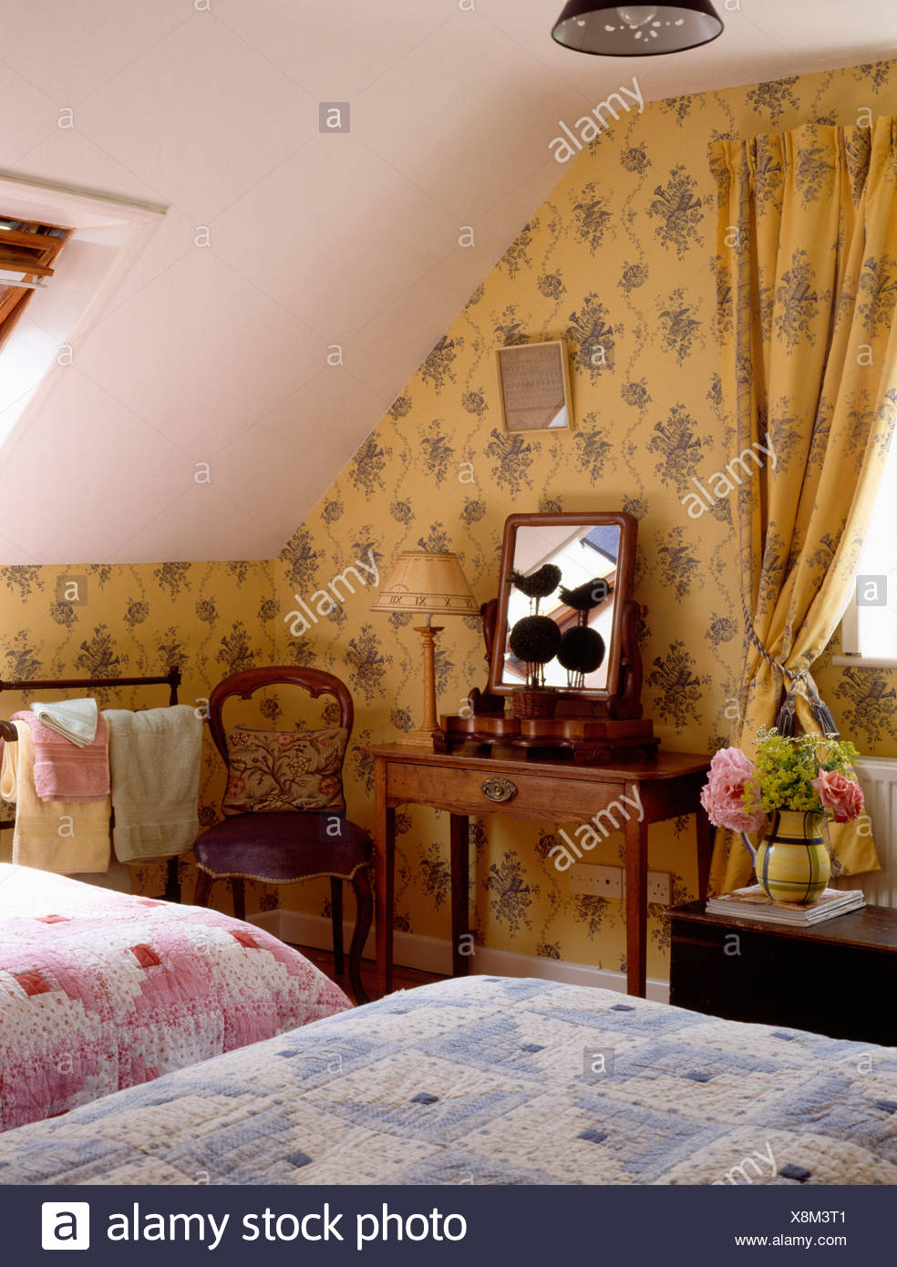 Floral Wallpaper And Matching Curtains In Cottage Attic Bedroom With Pink And Blue Quilts On Twin Beds Stock Photo Alamy