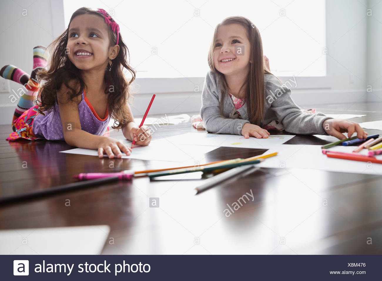 Smiling girls lying on floor coloring at home - Stock Image