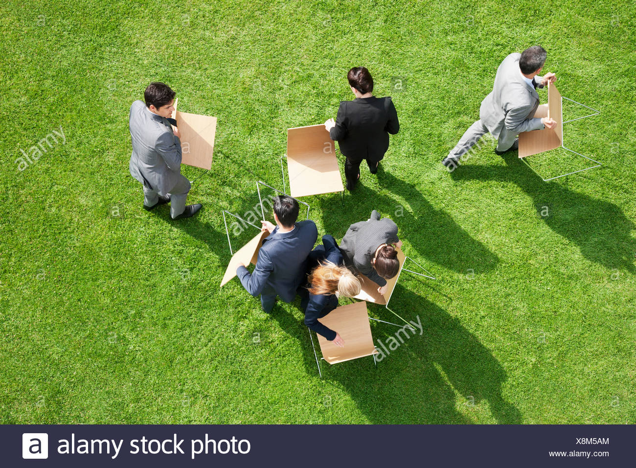 Business people carrying chairs outdoors - Stock Image