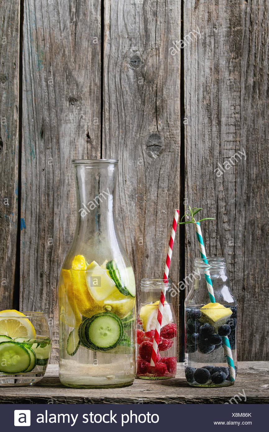 Citrus cucumber berries blueberry and rasberry sassy sassi water for detox in glass bottles with cocktail tubes on wooden background. Clean eating, he - Stock Image