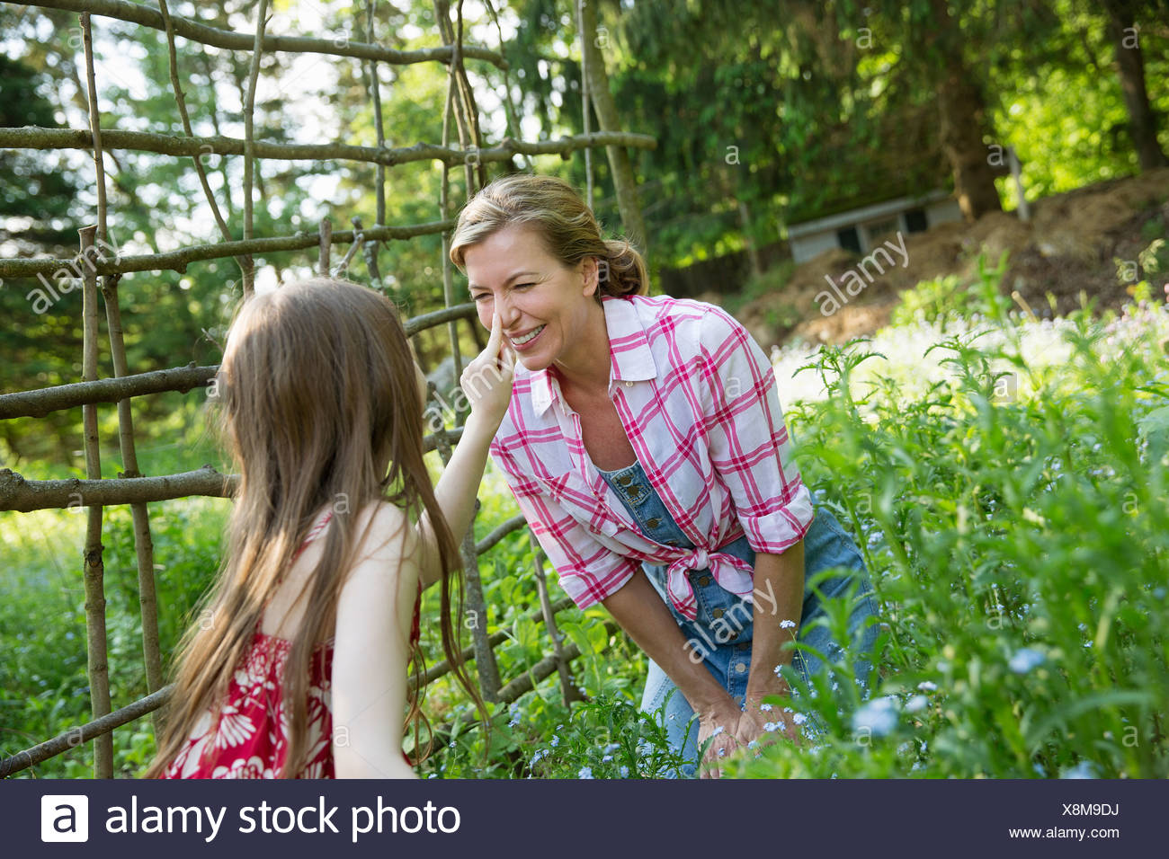 A mother and daughter together in a plant enclosure in a garden. Green leafy plants. A child touching the adult woman's nose. - Stock Image