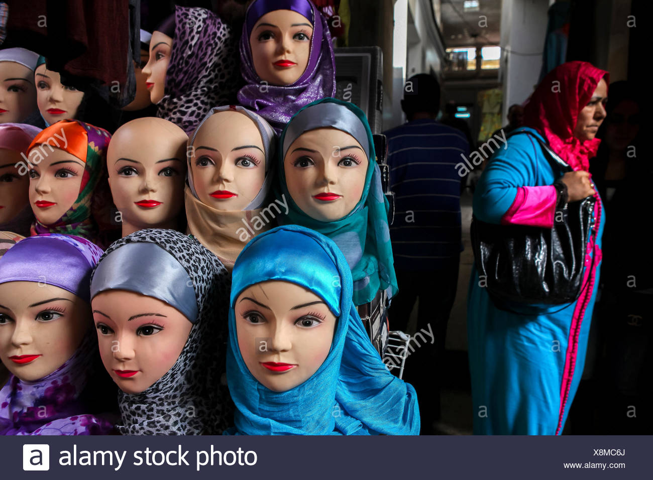 A woman walks past a selection of mannequin heads displaying hijabs in Fez, Morocco. - Stock Image