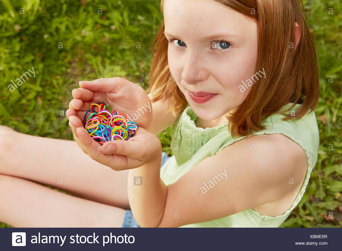 Portrait of girl in garden holding up rubber bands - Stock Image