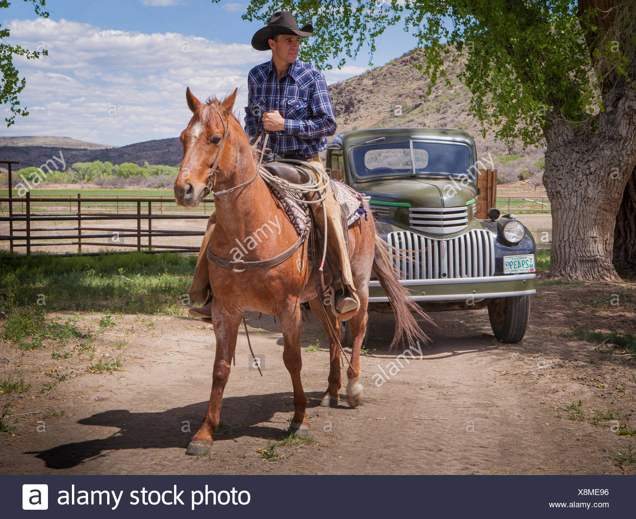 Cowboy riding horse near old antique truck Stock Photo