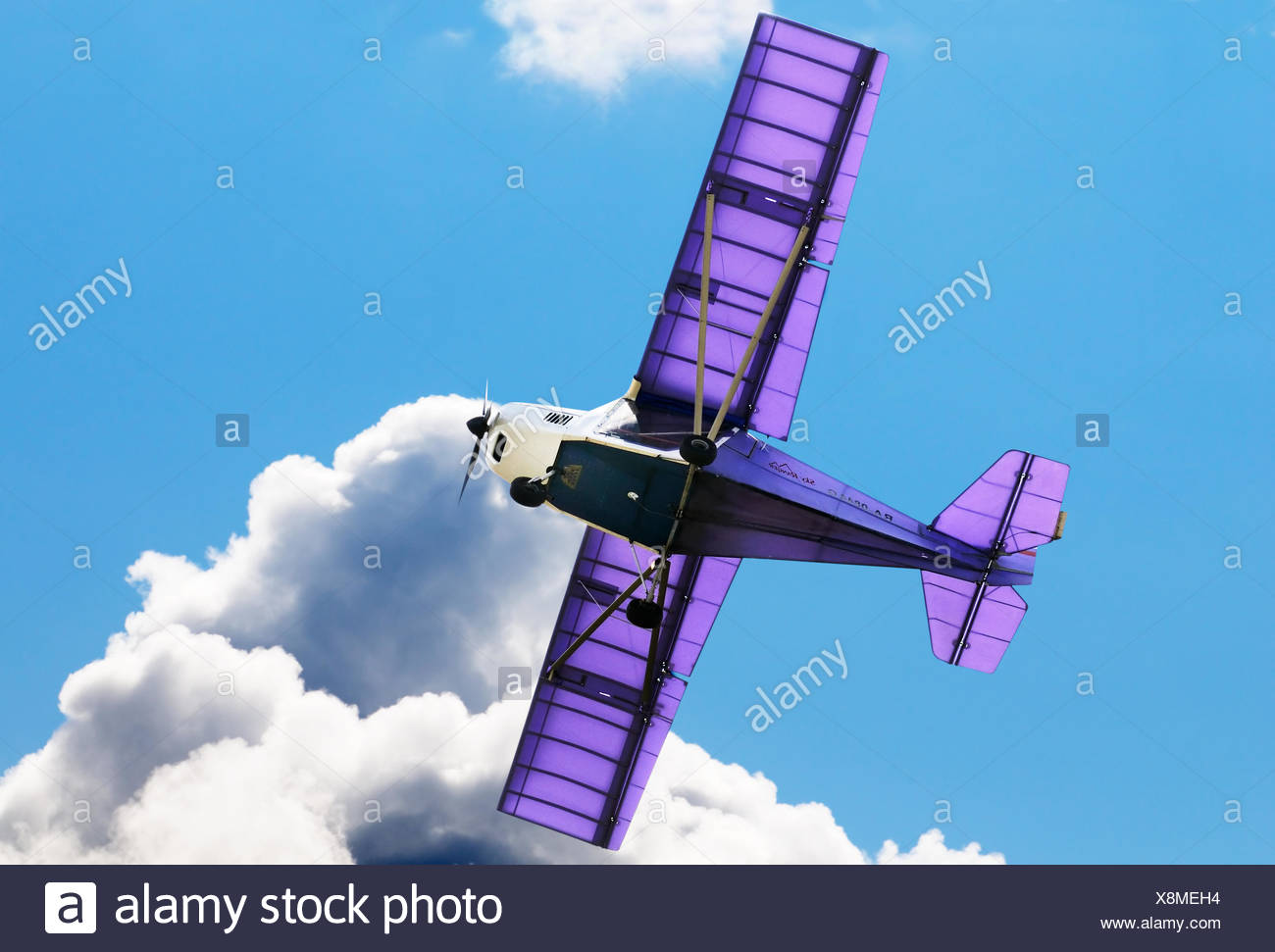 Flying private propeller-driven airplane over blue sky - Stock Image