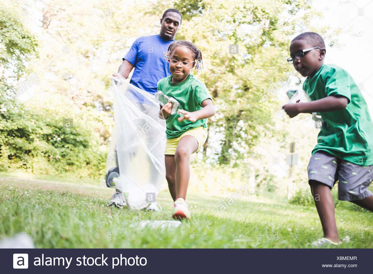 Father picking up litter with son and daughter at parkland eco camp - Stock Image