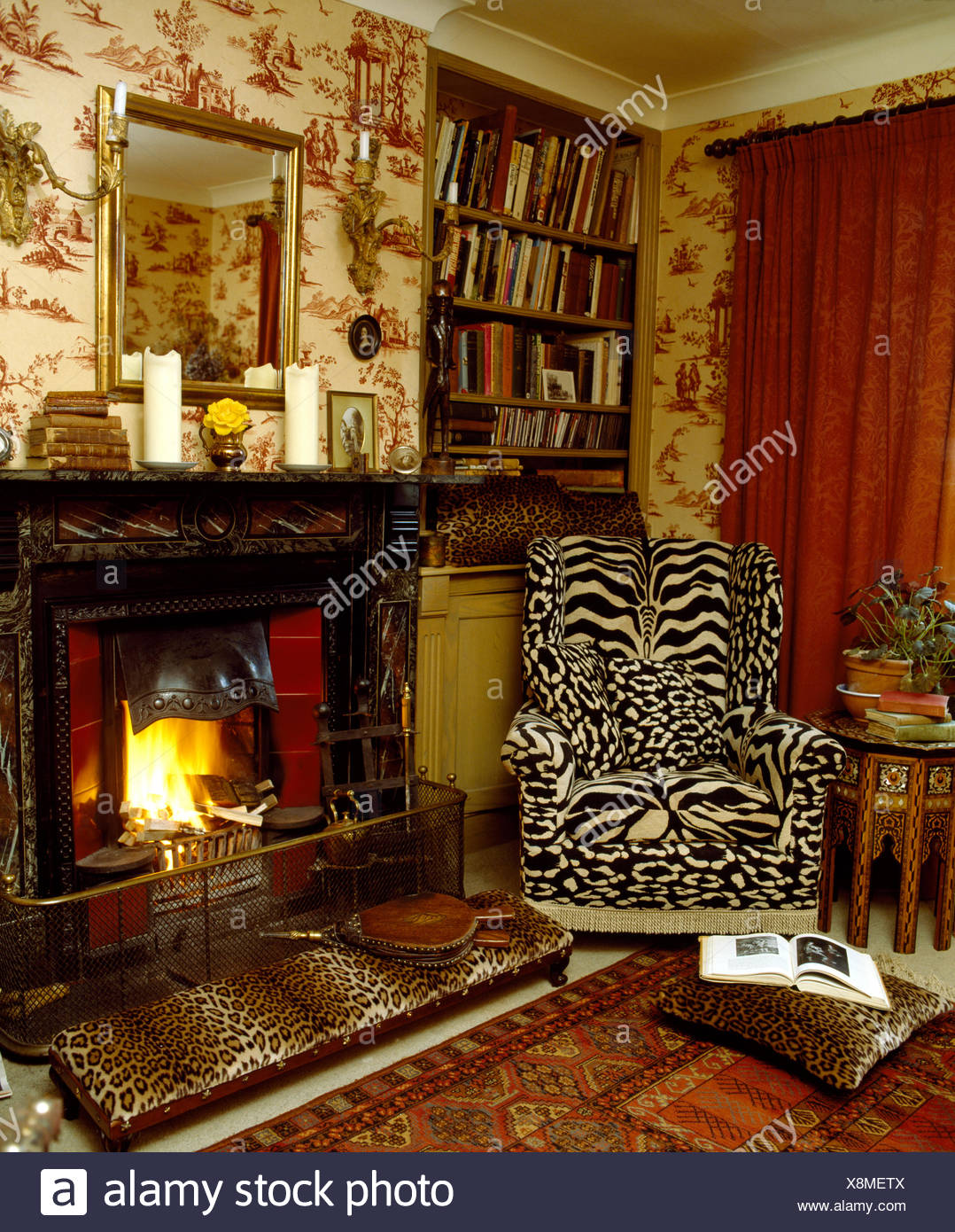 Tiger print wing chair and leopard print stool beside ...