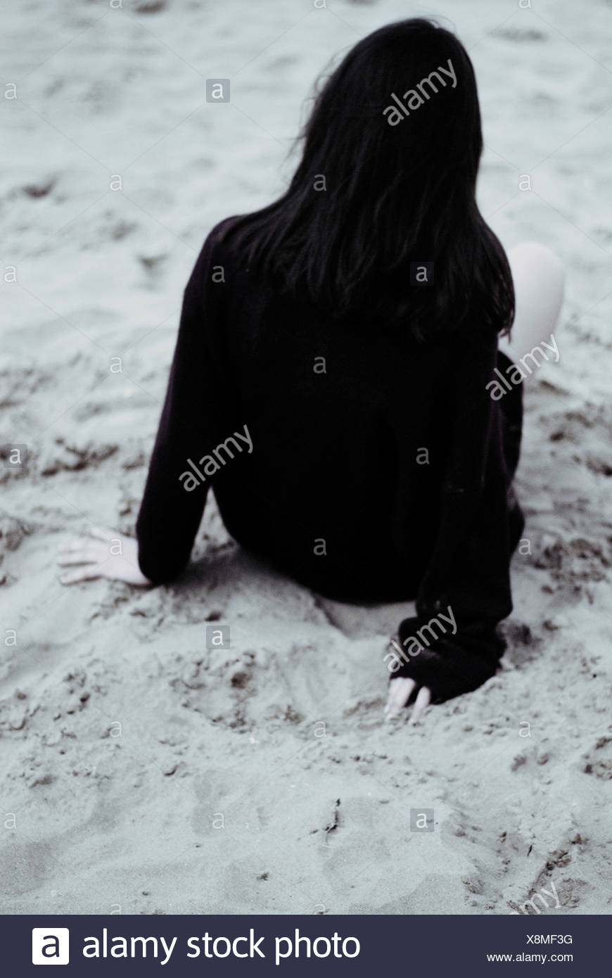 A young woman with black hair wearing a black sweater sitting on the sand - Stock Image