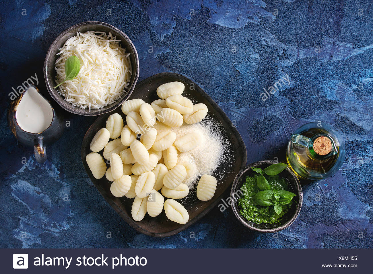 Raw uncooked potato gnocchi in black wooden plates with ingredients. Flour, grated parmesan cheese, pesto sauce, jug of cream, olive oil over dark blu - Stock Image