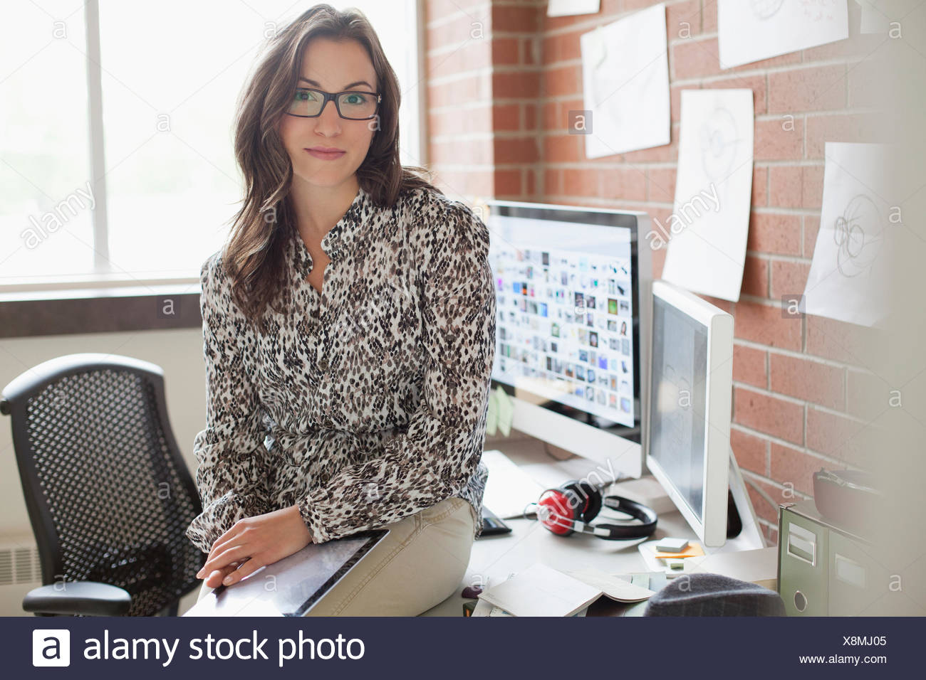 pretty, female industrial designer working in office - Stock Image