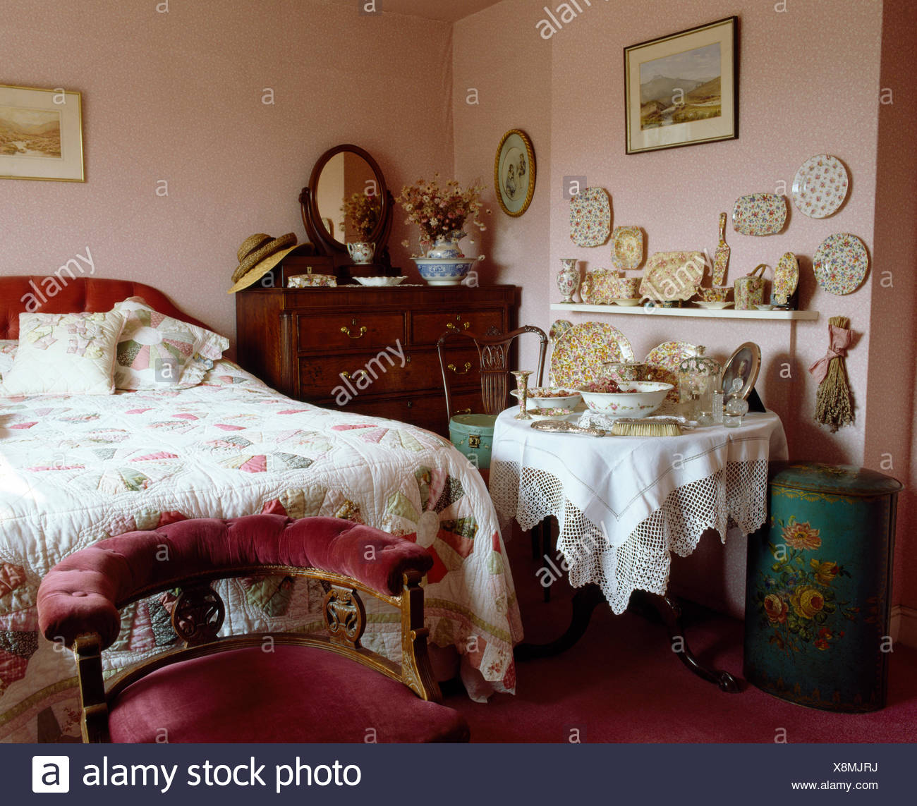 Pink velvet upholstered chair below bed with patchwork quilt in ...