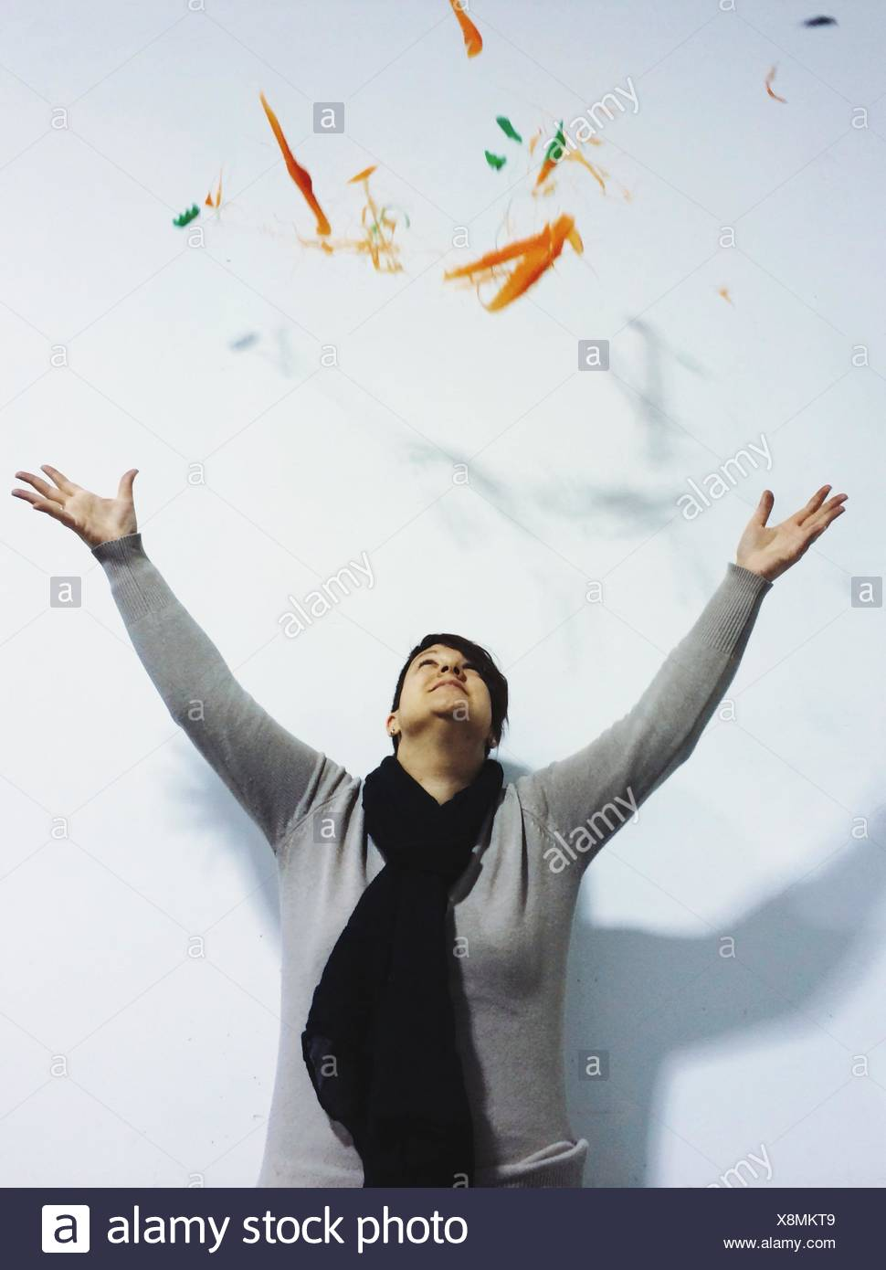 Young Woman Throwing Colored Particles Against White Background - Stock Image