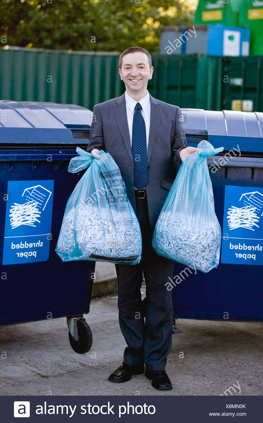 A businessman recycling bags of shredded paper - Stock Image