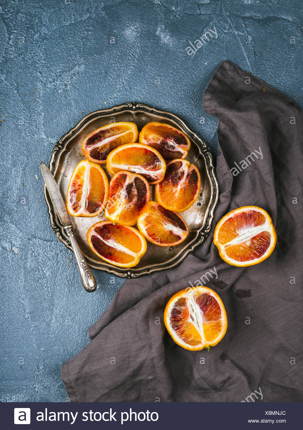 BLOODY RED SICILIAN ORANGES CUT INTO QUARTERS IN VINTAGE METAL PLATE OVER CONCRETE TEXTURED BACKGROUND - Stock Image
